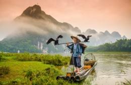 Älterer Mann in China steht auf seinem Floß