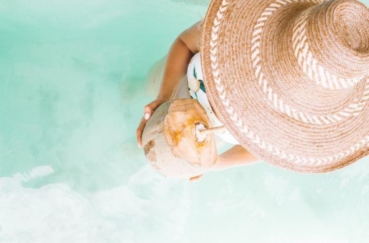 Frau mit Sonnenhut und Kokosnuss in der Hand am Strand