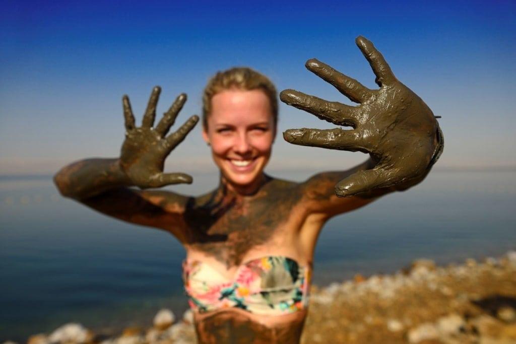Frau im Toten Meer mit schlammigen Händen