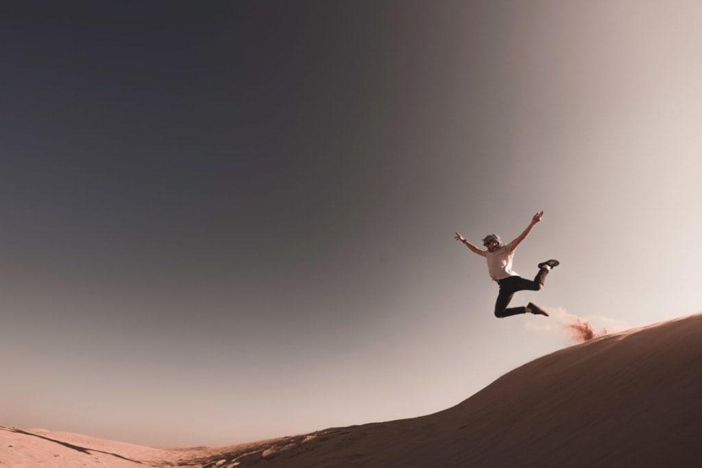 Frau springt durch Wüste