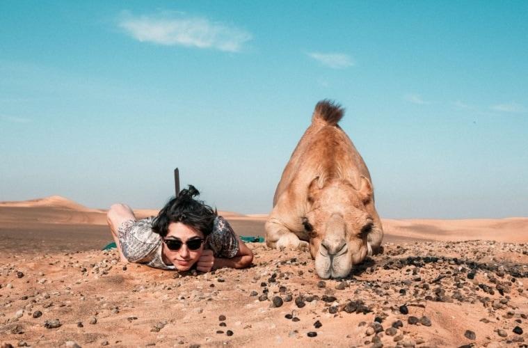 Frau und Kamel auf Boden liegend in der Wüste