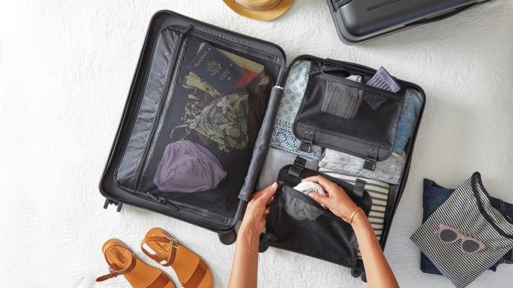 Zwei Hände packen packen aufgeklappten Koffer