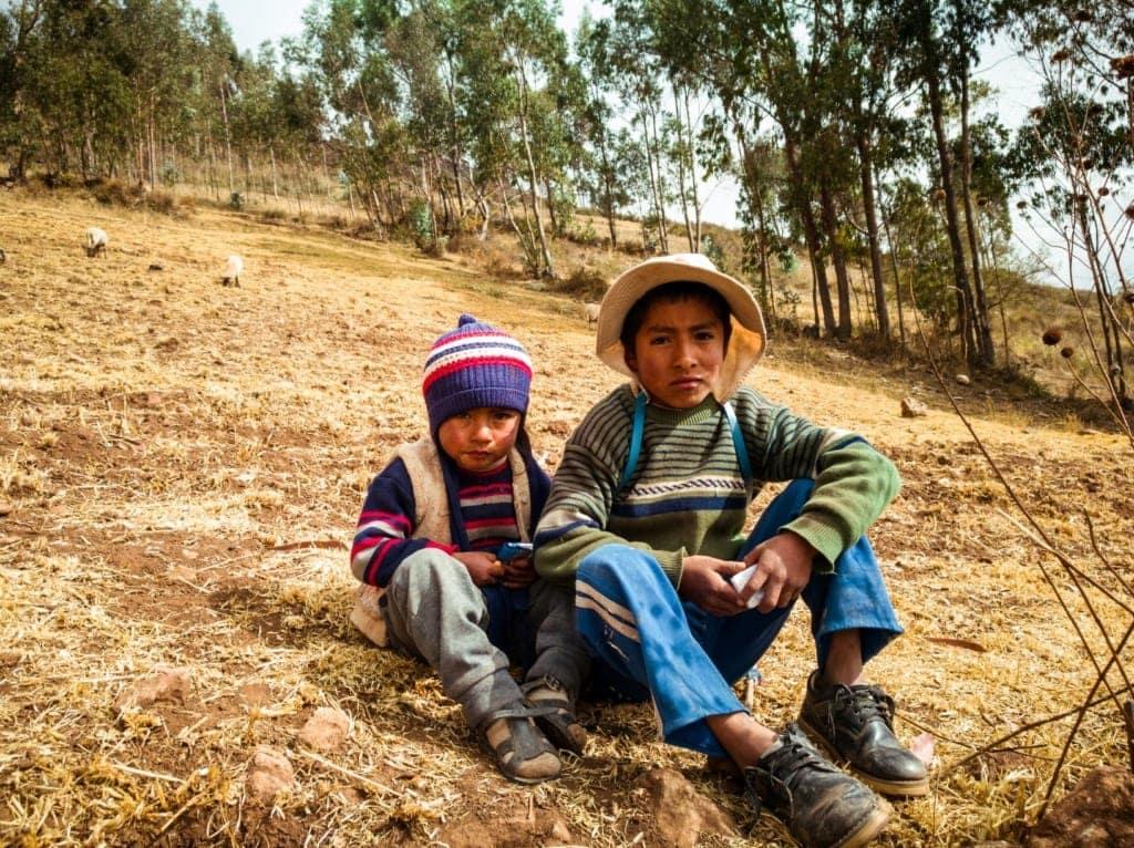 Zwei Jungen sitzen in Peru auf einer Wiese