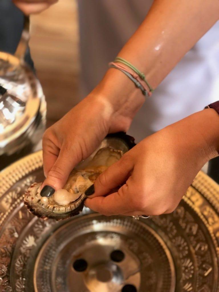 Frau hält Muschel mit Perle in der Hand
