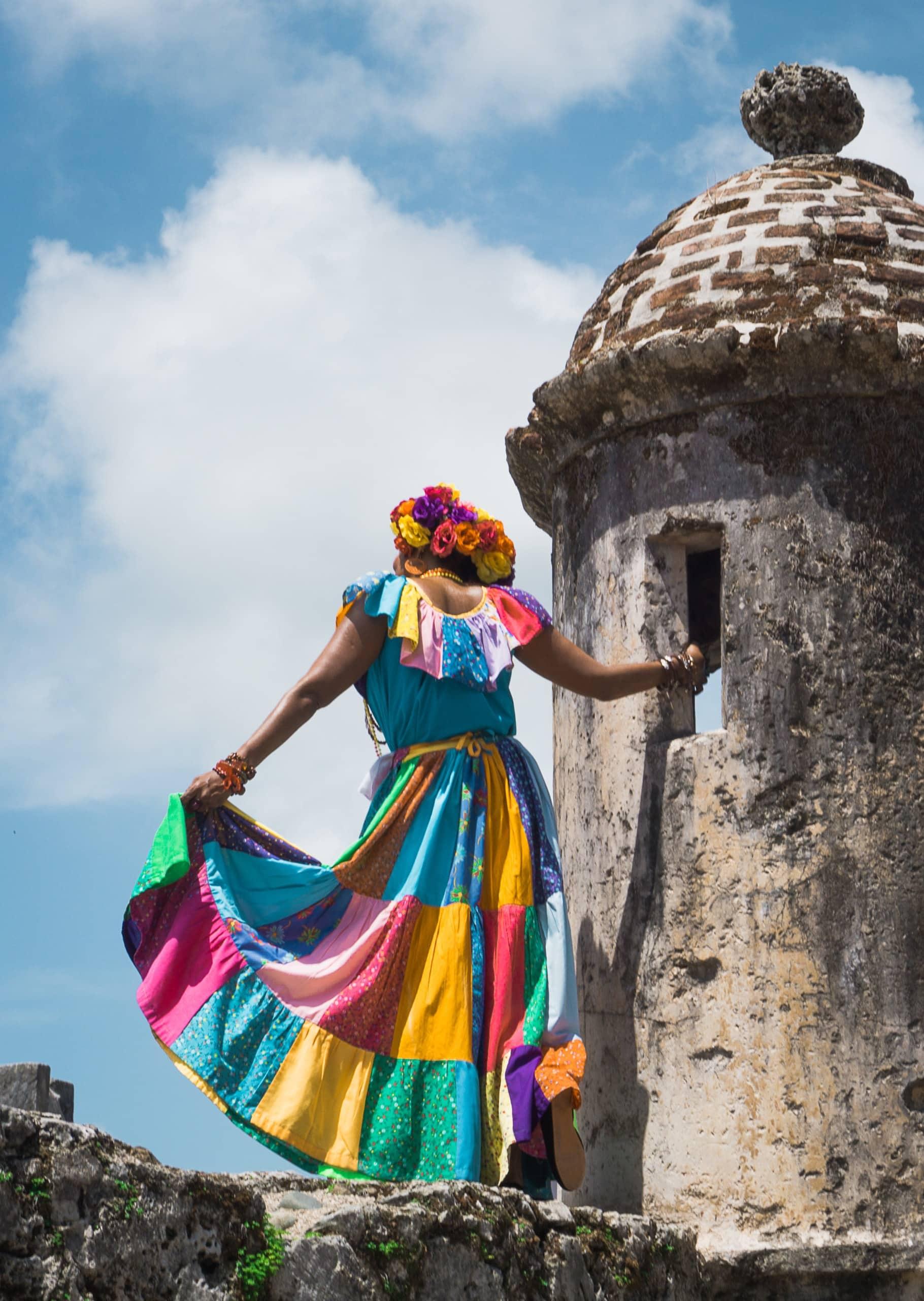 Frau in buntem Kleid blickt über Stadtruine