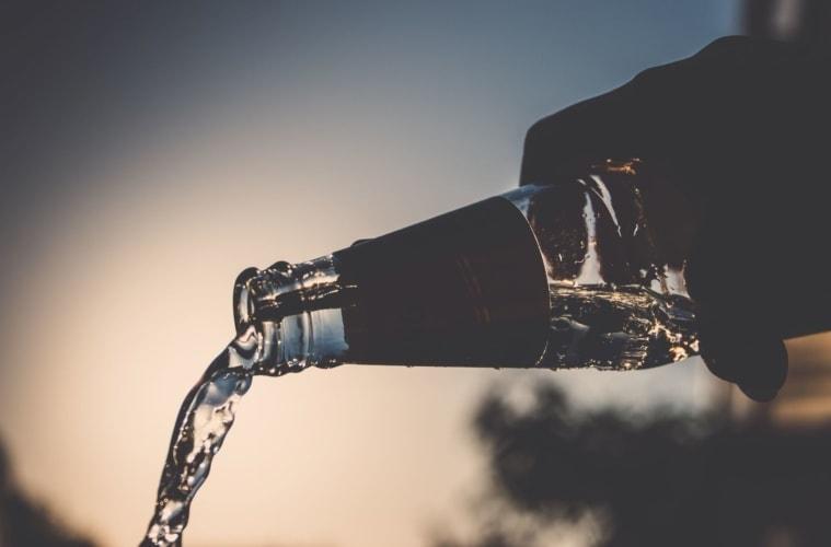 Jemand schüttet Wasser aus einer Flasche