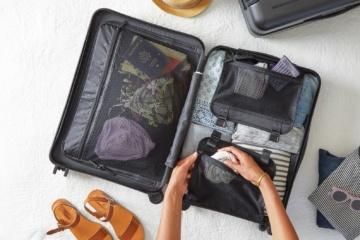 Geöffneter Koffer liegt auf Bett