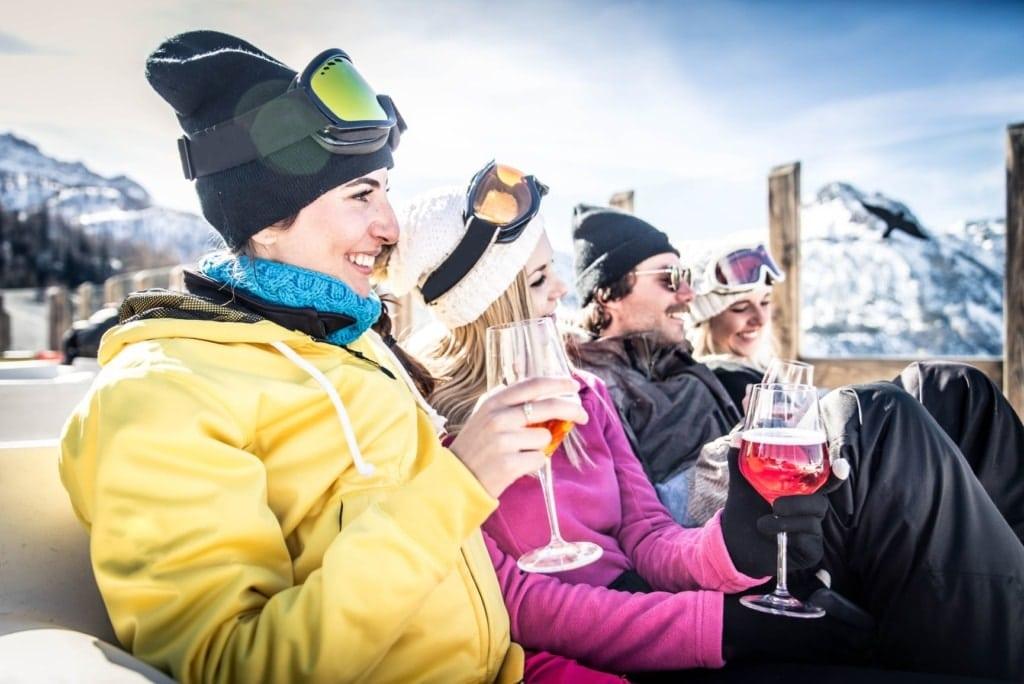Skifahrer sitzen auf einer Terrasse und trinken Alkohol