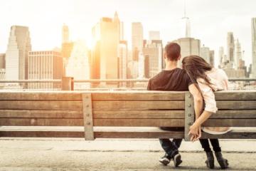 Paar sitzt auf Bank und betrachtet das New Yorker Panorama