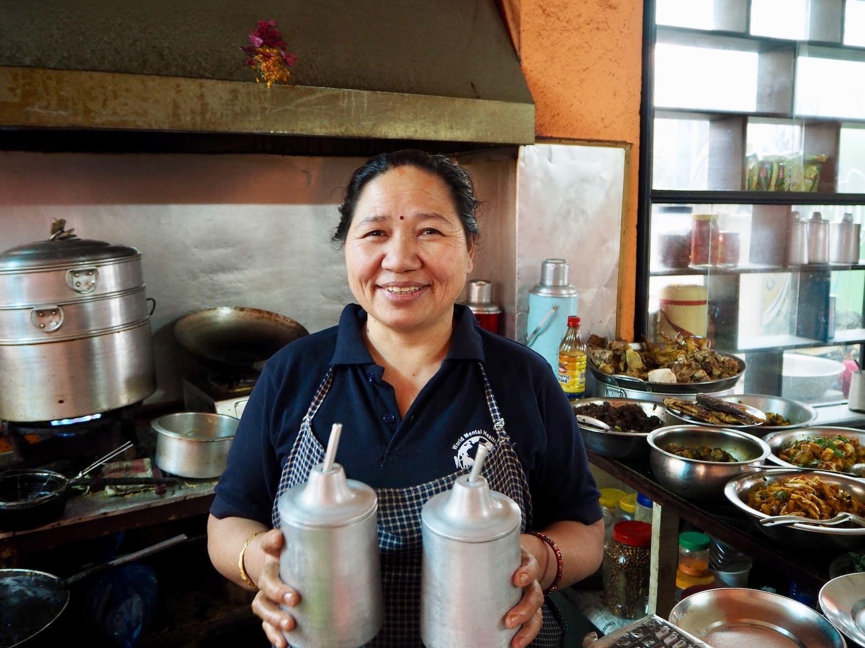 Nepalesische Köchin hält zwei Heißgetränke und lächelt in die Kamera