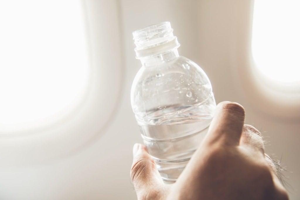 Hand eines Mannes hält Plastikflasche mit Wasser