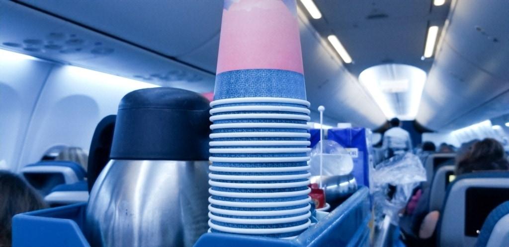 Pappbecher und Kaffeekanne auf Trolley im Flugzeug