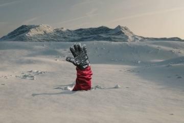 Skifahrer streckt Hand aus Schnee