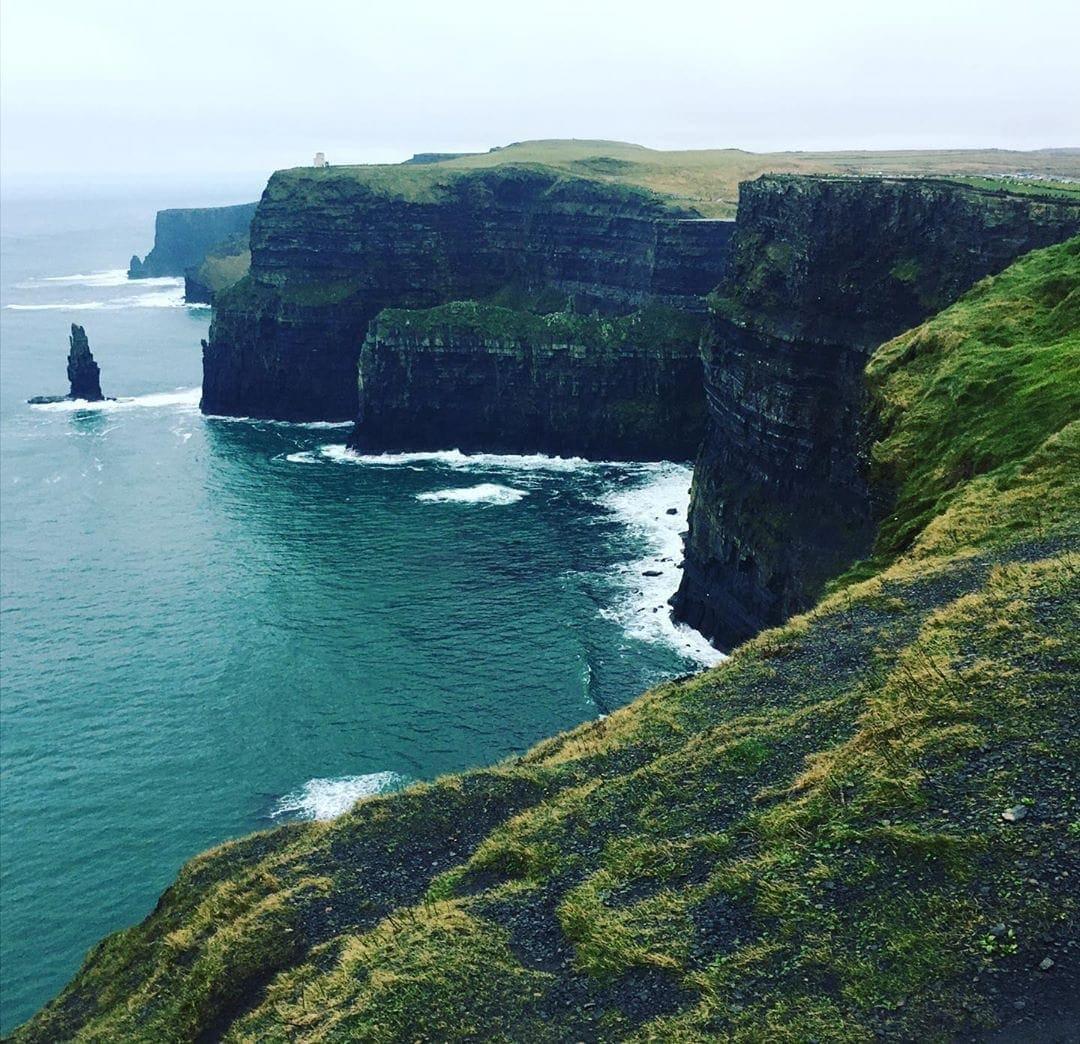 Für dieses Foto musste sich Redakteurin @marie.worldwild ganz schön überwinden: Über 200 Meter fallen die moosbewachsenen Steilklippen bei Galway in die Tiefe! Eine wilde Wucht, dieses Irland, findet sie. Doch egal für welche Jahreszeit gilt – Regenjacke und matschfeste Schuhe nicht vergessen! #ireland #irland #cliffsofmoher #comewithme #wildatlanticway #meer #passionpassport #travel #traveldeeper #wild #reporterontour #reisen #galway #galwayireland