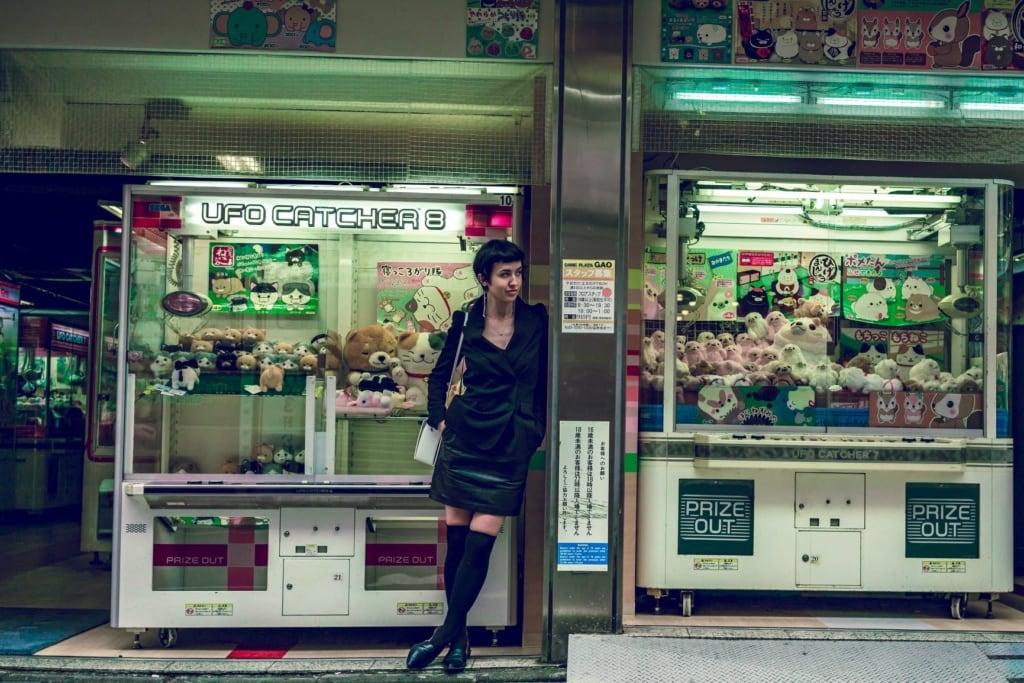 Frau vor Plüschtierautomaten in Tokio