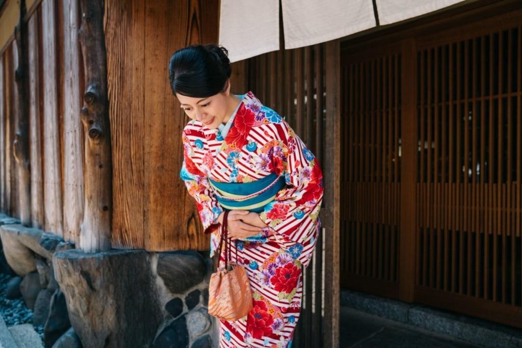 Japanische Dame, die sich vor ihrem Haus mit einem Kimono bowing