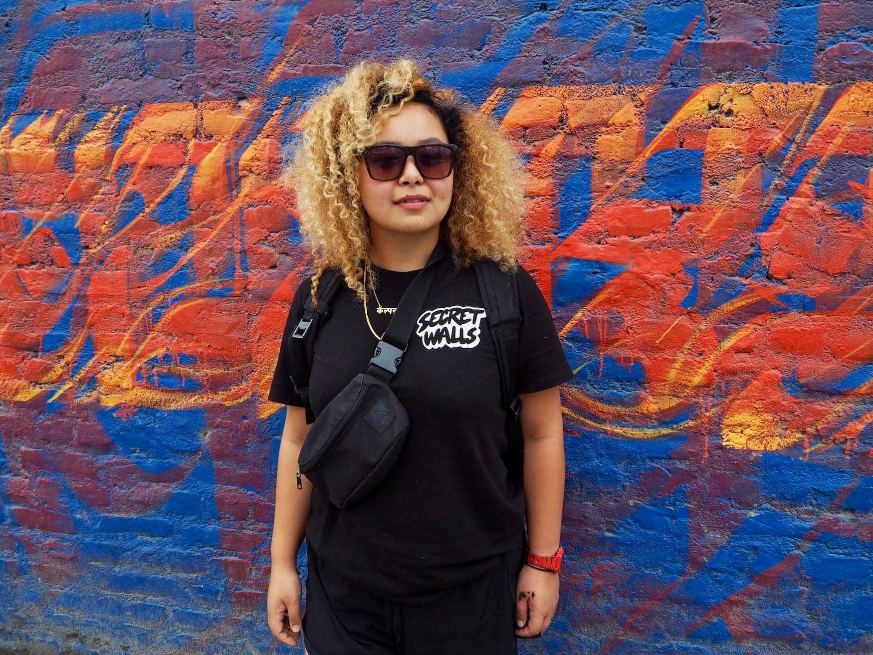 Street-Art-Künstlerin aus Kathmandu vor Graffiti
