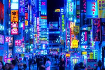 Belebte Straße mit bunten Reklameschildern in Shinjuku, Tokio