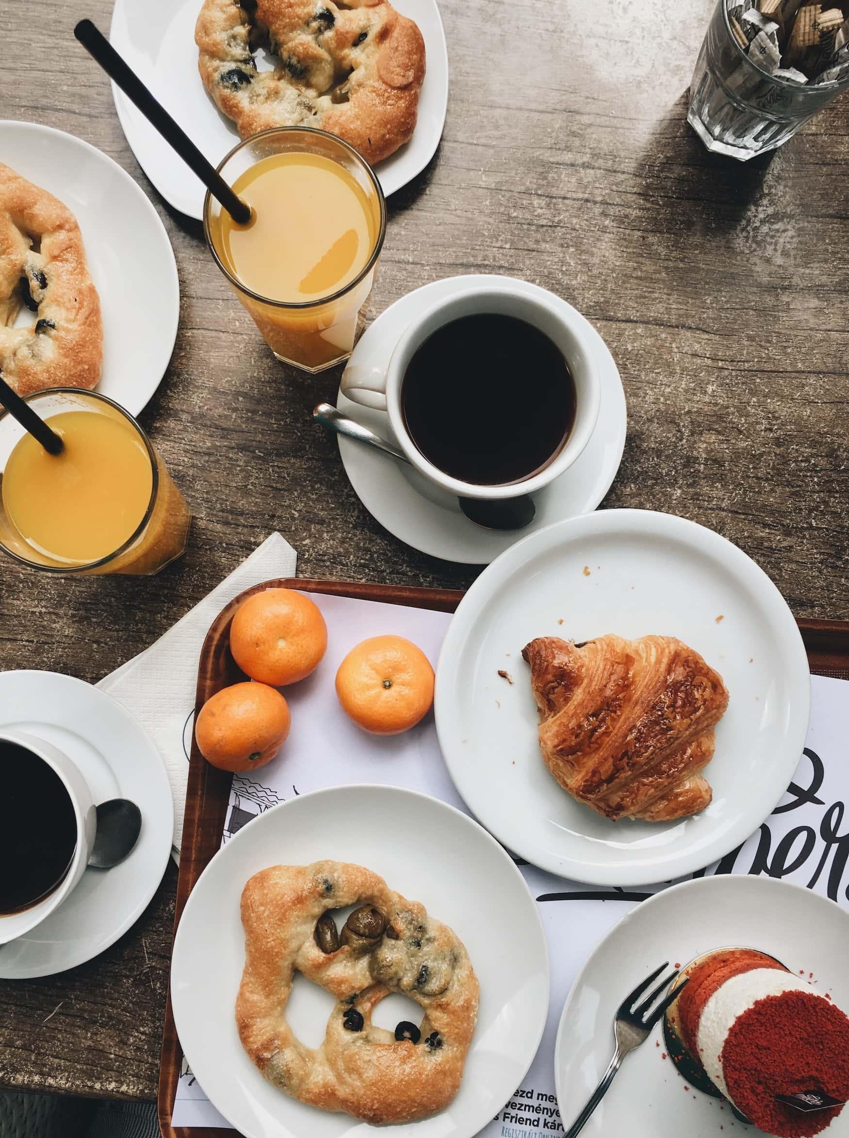 Frühstück mit Kaffee, Orangensaft und süßem Gebäck
