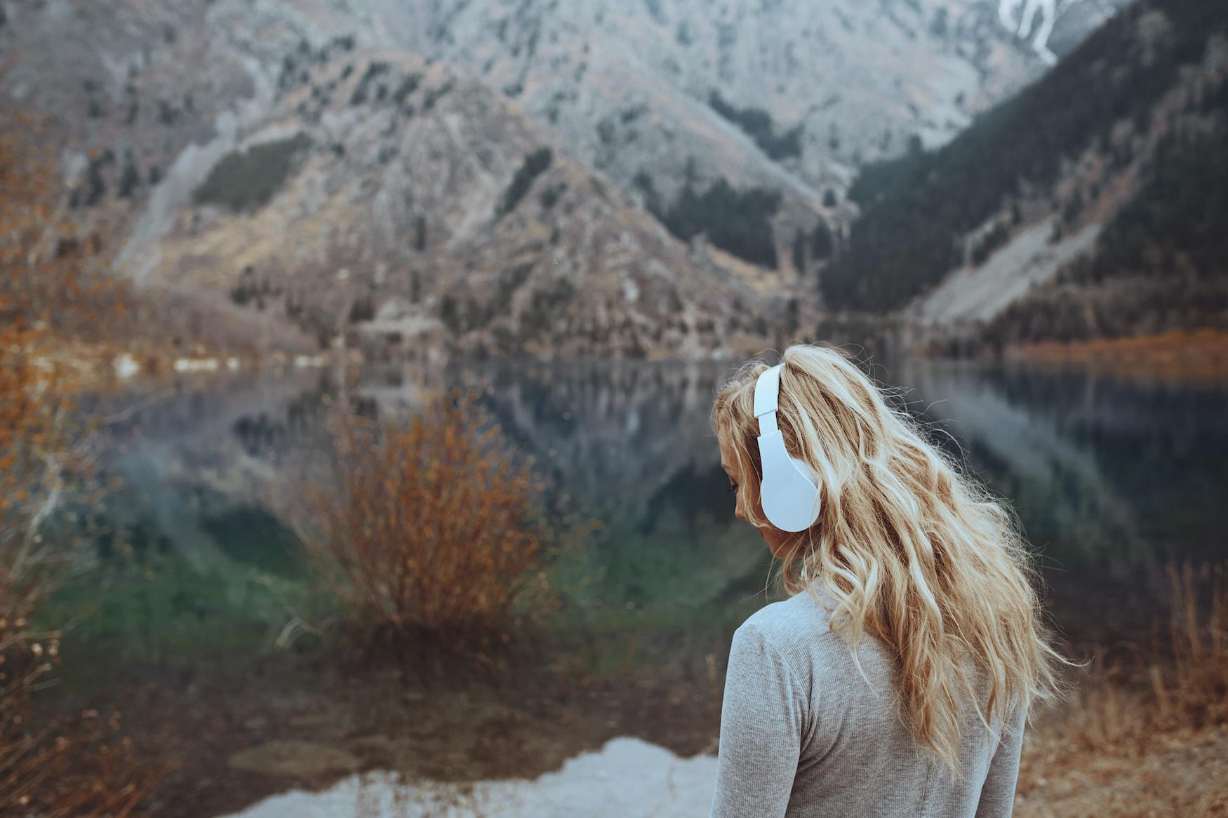 Frau mit großen weißen Kopfhörern steht vor Bergkulisse