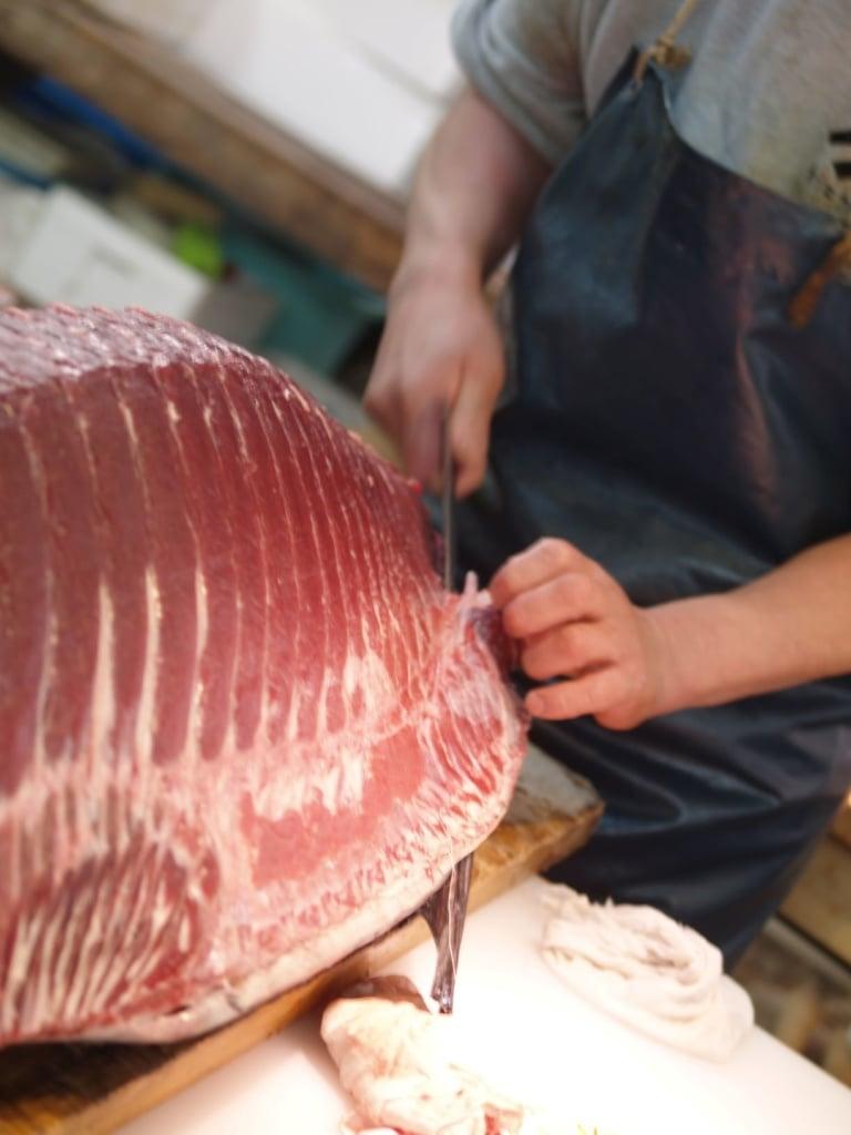 Mann schneidet großes Stück Fisch auf dem Fischmarkt in Tokio