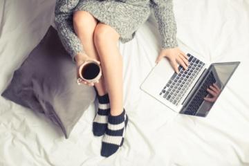 Frau sitzt im Bett, hält Tasse Kaffee in der Hand, und bedient Notebook