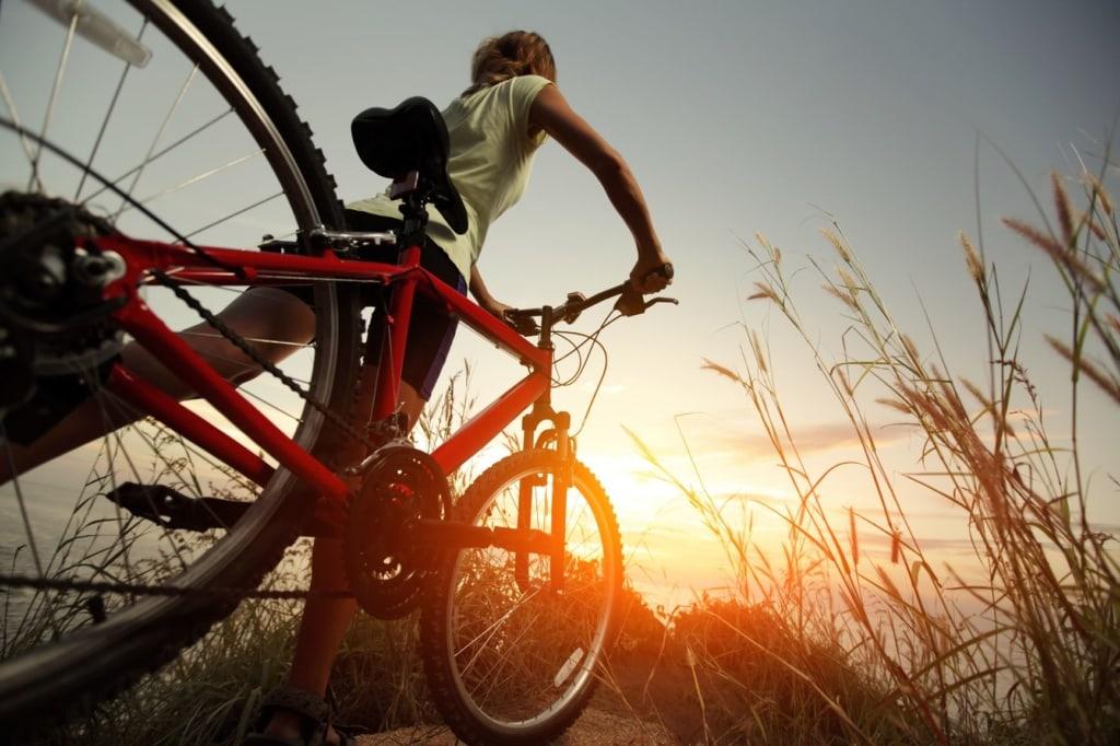 Frau schiebt Fahrrad in der Natur, Küste