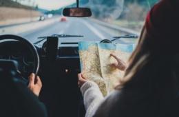 Beifahrerin hält Landkarte und zeigt auf einen Ort während der Mann das Steuer hält und fährt