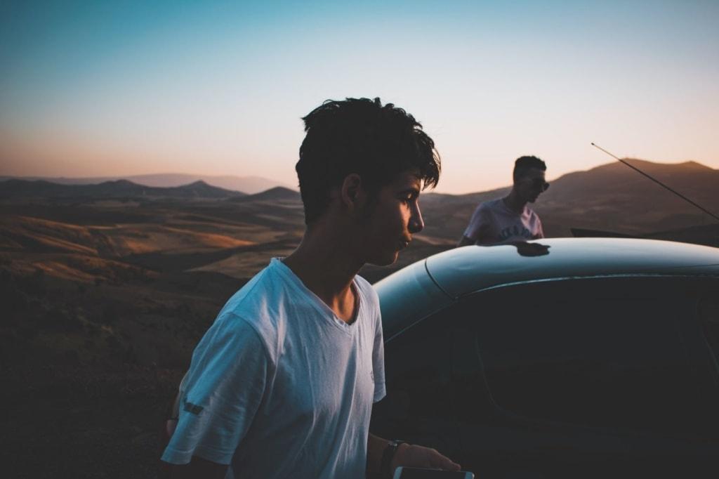 Zwei junge Männer steigen in Auto ein, Hintergrund Mond-Landschaft