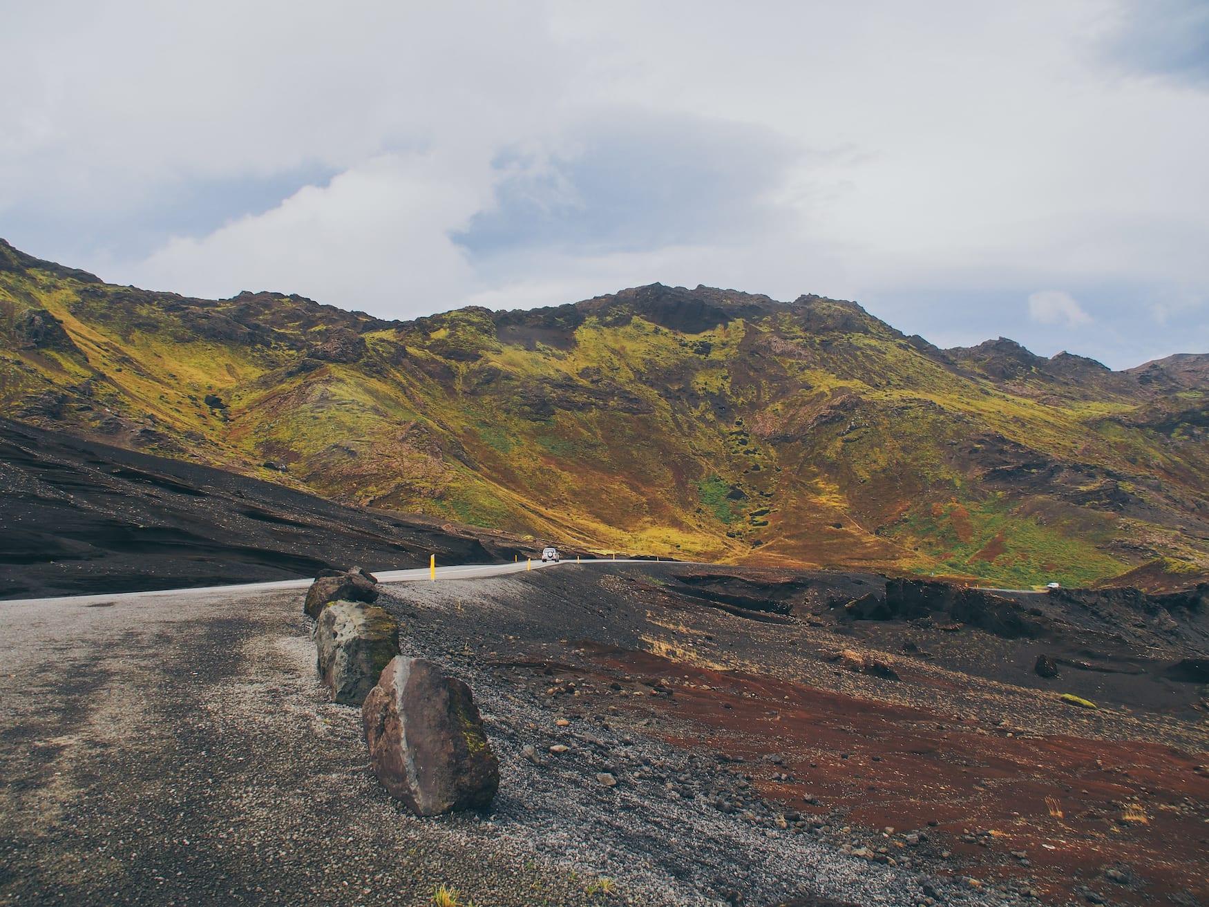 Auto fährt über isländische Landstraße, die rundherum von bunten Gesteinen umgeben ist