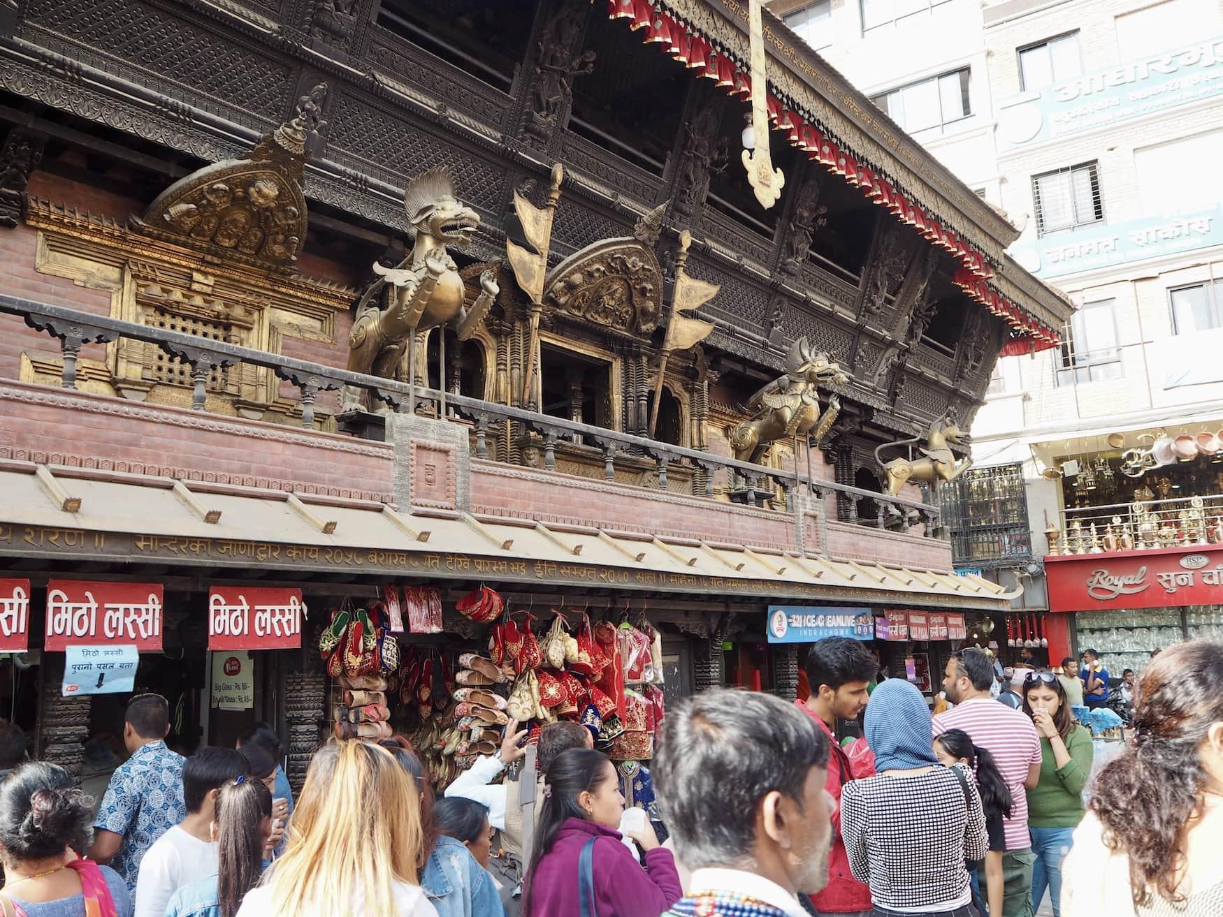 Menschen drängen sich durch Straße in Kathmandu