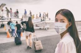 Reisende mit Mundschutz in Coronavirus-Zeiten