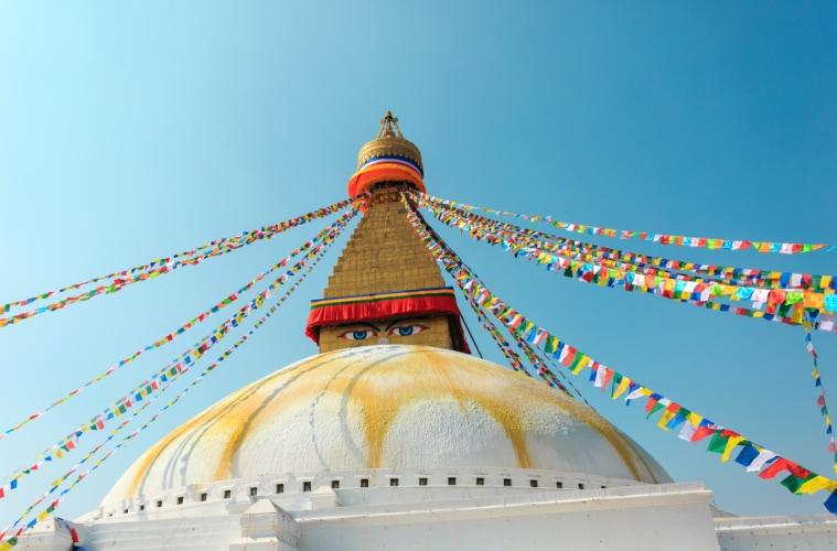 Tempelspitze, die mit bunten Fahnen und Gesicht-Malerei versehen ist, in der Hauptstadt Nepals: Kathmandu