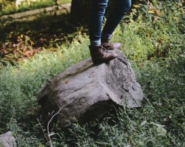 Wanderer steht in der Natur auf einem großen Stein