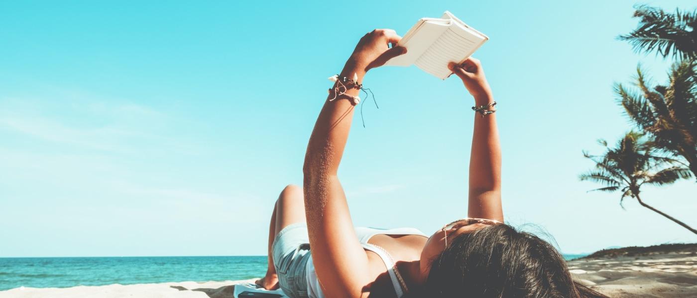 Mädchen liegt am Strand und liest ein Buch