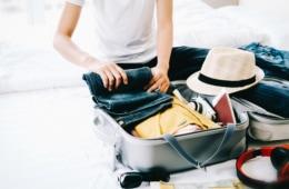 Mann rollt seine Jeanshose, um sie in seinen Koffer zu packen