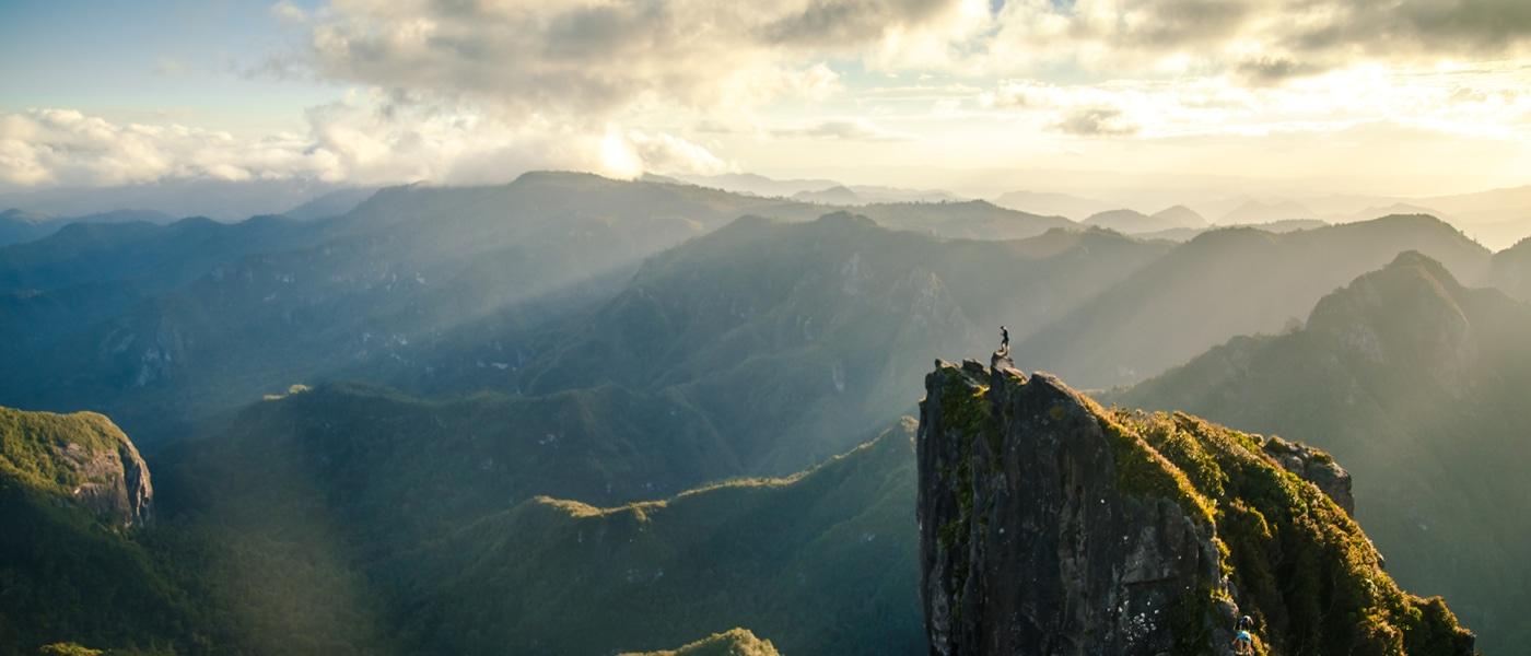 Mann auf Bergspitze in Neuseeland