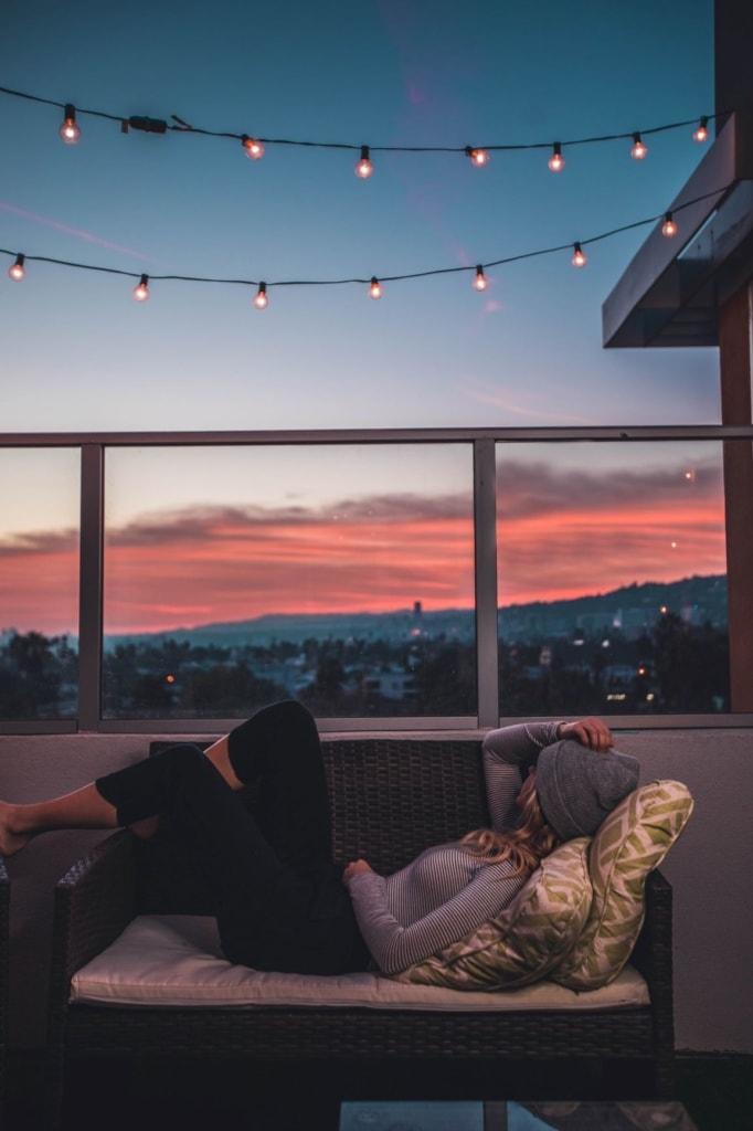 Frau liegt auf Bank auf Balkon