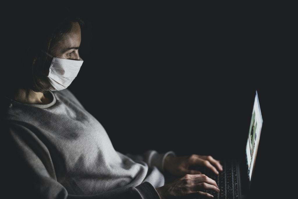Fliegen in Zeiten der Coronakrise: Frau mit Mundschutzmaske bedient Notebook