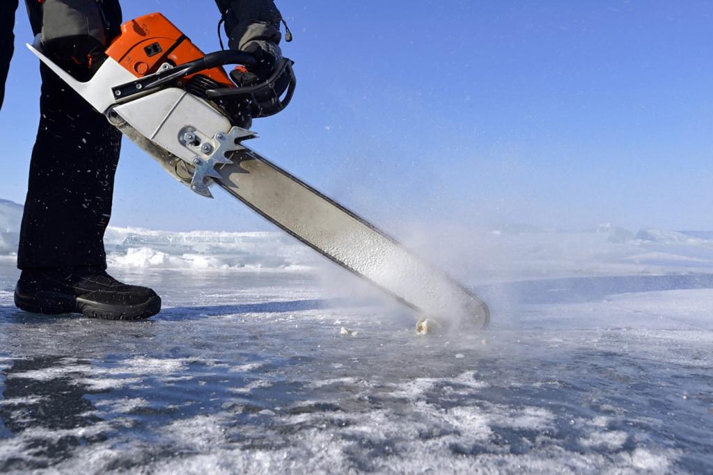 Mit einer Kettensäge wird ein Loch in die Eisdecke des Baikalsees gefräst, damit die Taucher einsteigen können.