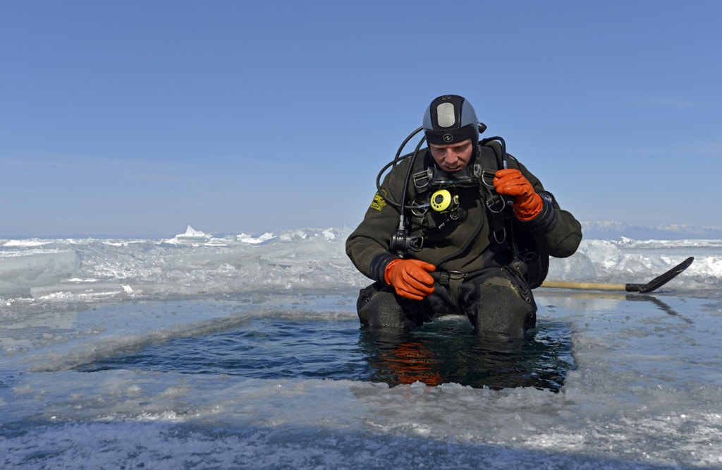 Und rein ins kalte Wasser: Der erste Taucher traut sich ins Eisloch im Baikalsee.