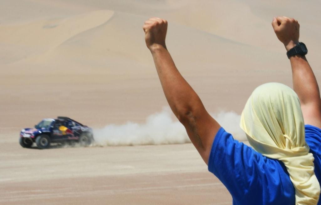 Zuschauer jubelt einem vorbeifahrenden Auto bei der Rally Dakar zu