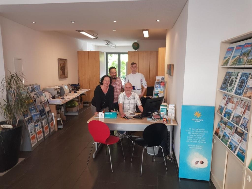 Jochen Volland mit Mitarbeitern in seinem Reisebüro Teddy Travel in Köln