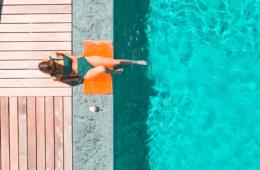 Frau am Beckenrand sitzend, hält die Füße in den Pool