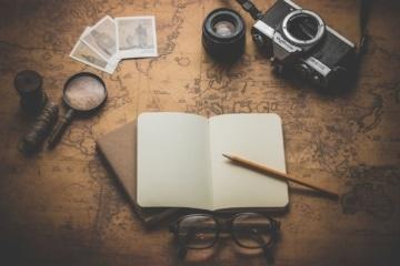Uralte Weltkarte, auf der Notizbuch, Kamera und Lupe liegen