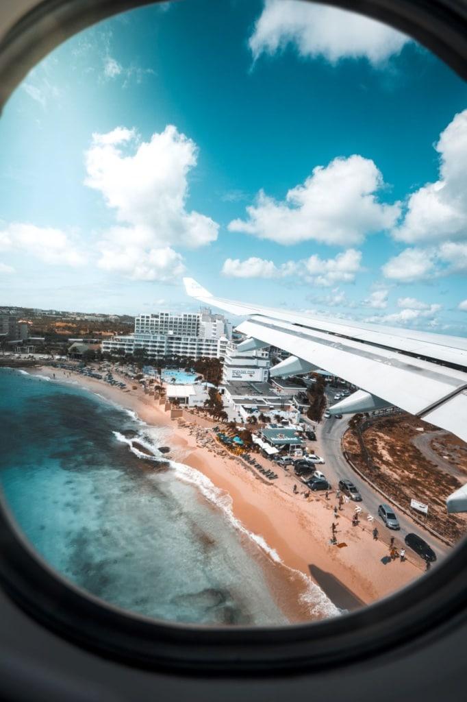 Blick auf Flugzeugfenster auf Strand St. Maarten