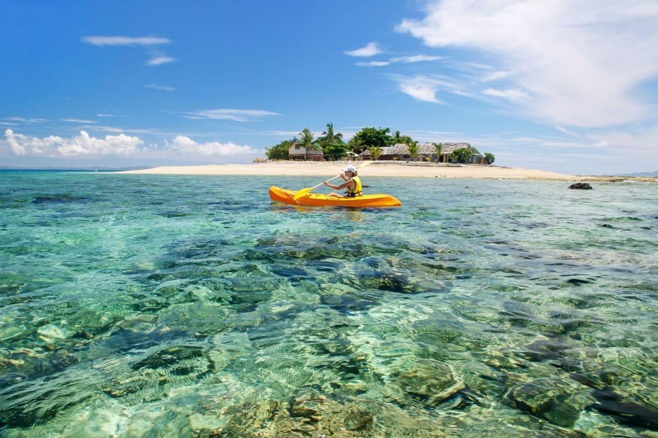 Junge Frau Kajak in der Nähe von South Sea Island, Mamanuca Inselgruppe, Fiji.