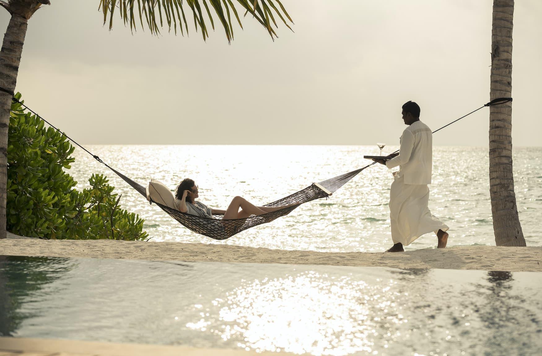 Frau liegt in Hängematten an Strandabschnitt auf der Privatinsel at Voavah auf den Malediven