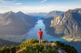 Mann blickt von Hügel auf Alpen und See in Österreich