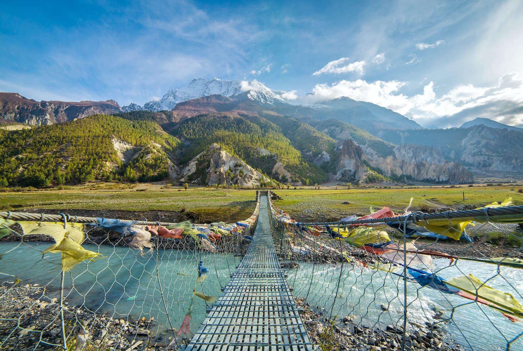 Gebetsflaggen schmücken eine Brücke in nepalesischer Landschaft